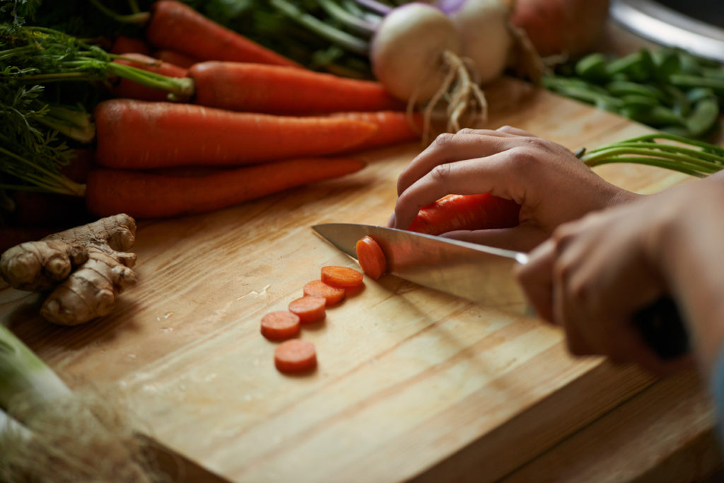 Shot of a woman cutting vegetables on a cutting board