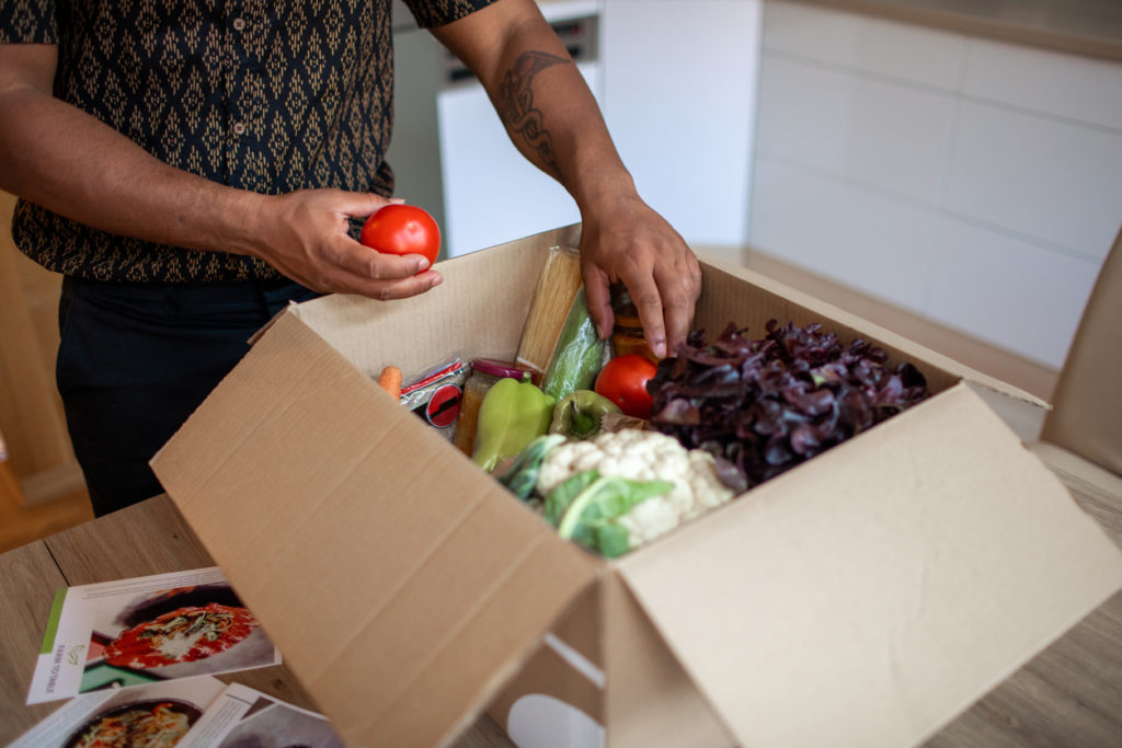 Man opening parcel with meal kit.