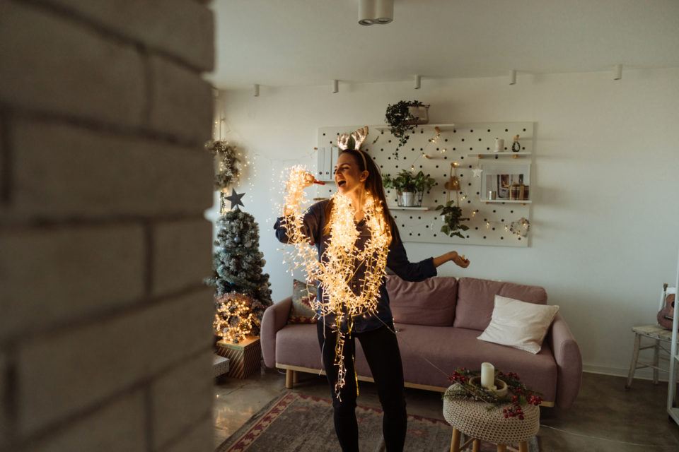 Photo of an excited young woman singing while decorating the living room of her apartment; wrapped in Christmas lights and wearing shiny reindeer antlers; preparing for the upcoming holidays.