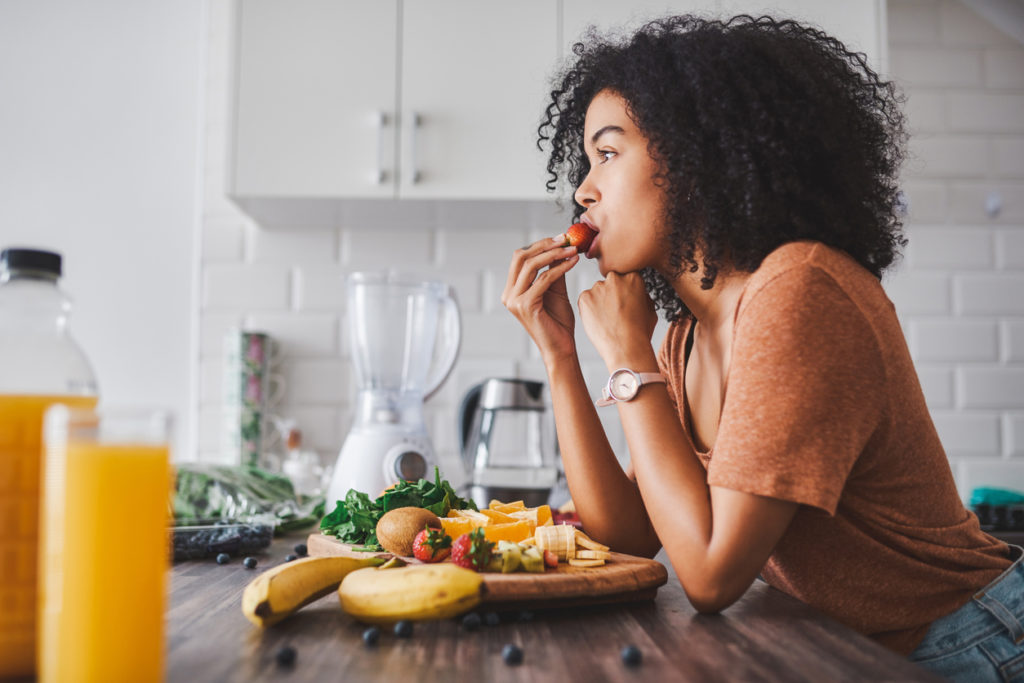 Shot of a young woman making a snack with fruit at home