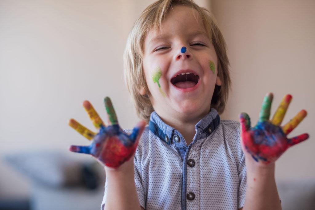 Cute little boy is having fun with finger paint