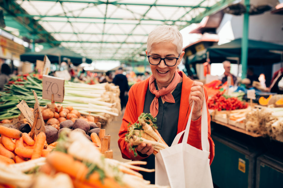 One elderly woman buying a bundle of carrots at a community marketplace