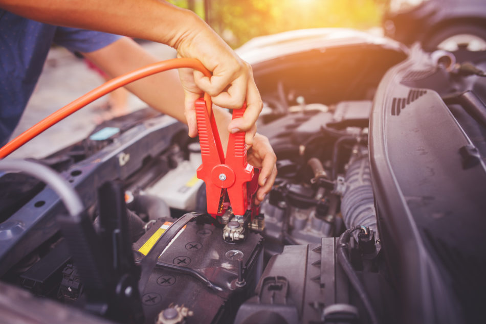 Close up of auto mechanic jumping battery